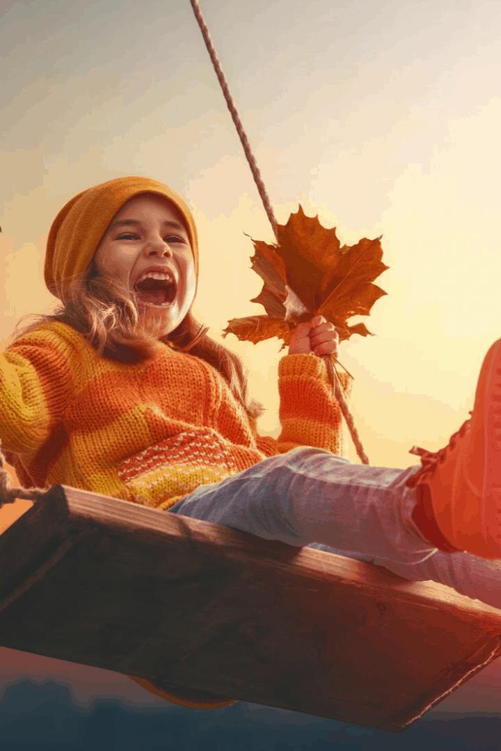 girl swinging in fall leaves